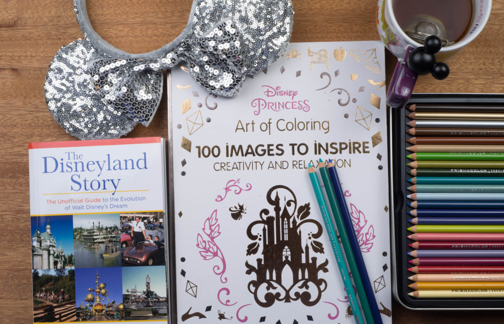 Disney Princess Art of Coloring Book and Colored Pencils with Sequin Mickey Ears and The Disneyland Story Book on a table
