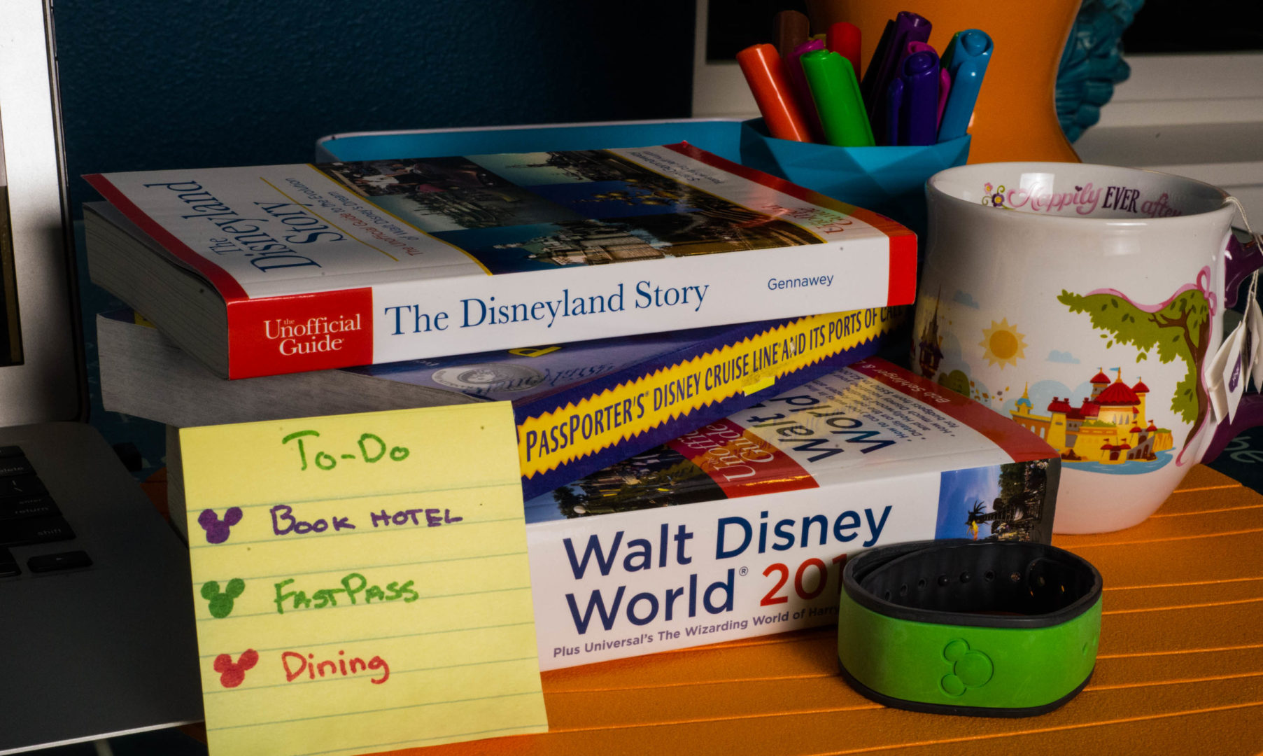 Stack of Disney Travel Guide Books with a To Do List and Magic Band